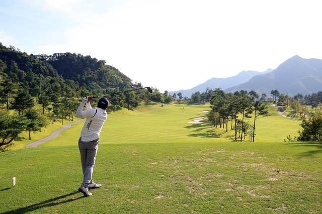 golfer tees off on wooded gold course