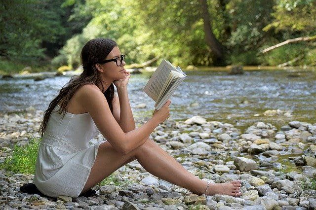 Young female student reading a book by the side of a stream