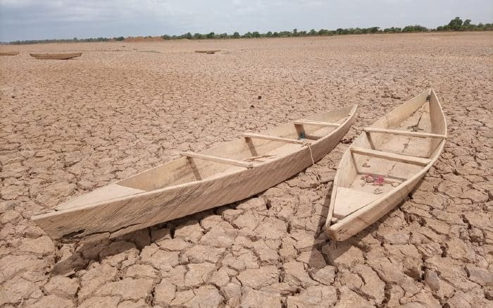 Two boats in a dried up lake.