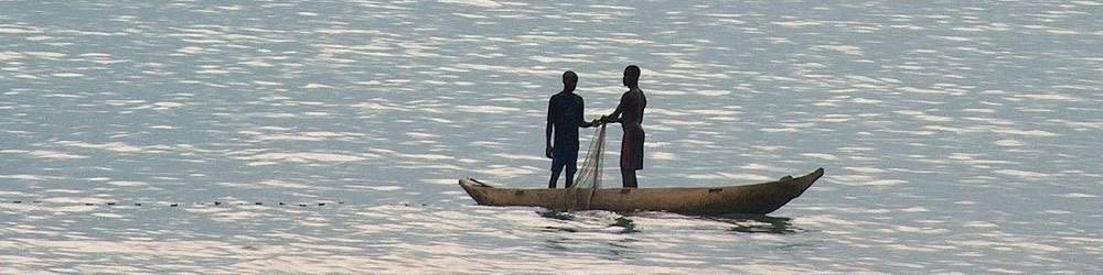 Two fishermen pulling in the nets in Sao Tom and Principe