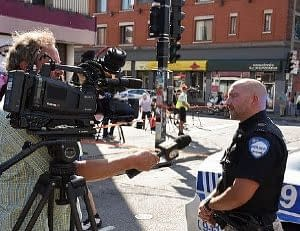 Local news 24/7. US policeman being interviewed in a New York street.